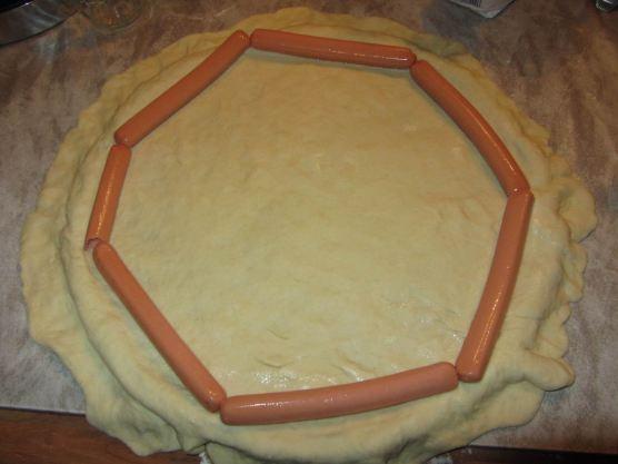 Etaler la pate à pizza sur une plaque ronde en dépassant légèrement et installer les knacki